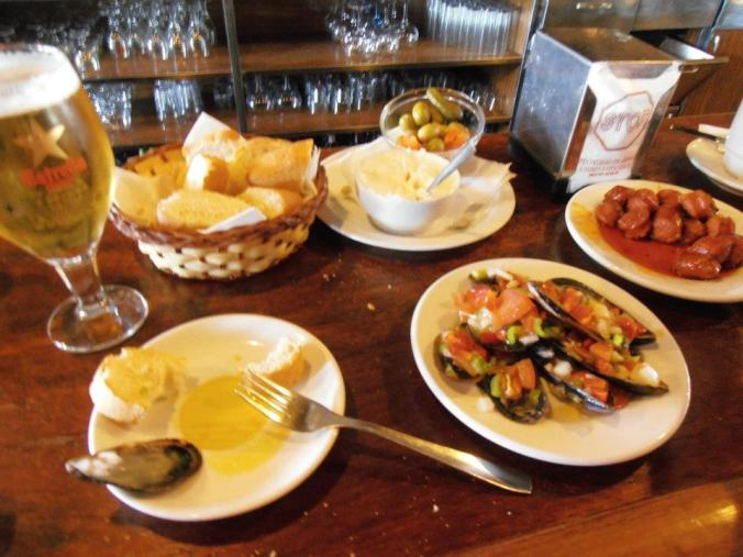 beer, olives & pickles, chorizo, mussels & bell pepper relish, and bread with a garlic spread. (Stop Cafe)
